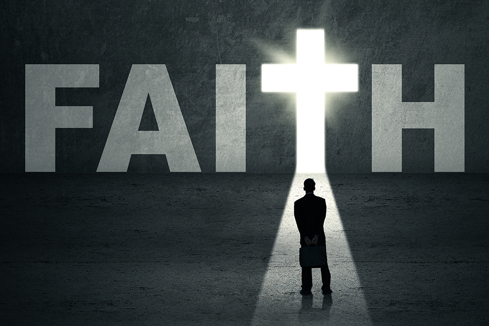 Man standing in the path that leads to the cross with the light coming through the word Faith